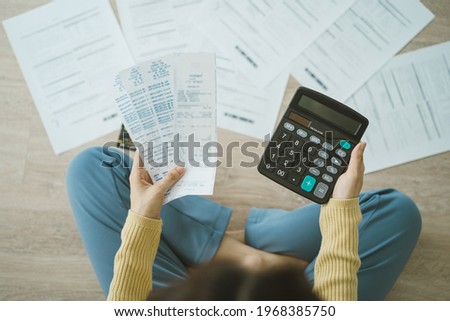 Top view owe asian woman, female sitting on floor stressed and confused by calculate expense from invoice or bill, have no money to pay, mortgage or loan. Debt, bankruptcy or bankrupt concept. Stockfoto ©