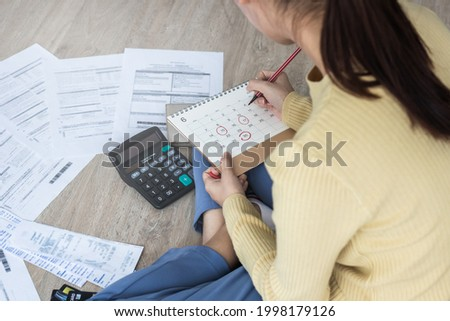 Top view owe, mortgage asian woman, female sitting on floor home, stressed calculate expense from bills, no money pay in mark circle deadline on calendar.Debt, bankruptcy or bankrupt person concept. Stockfoto ©