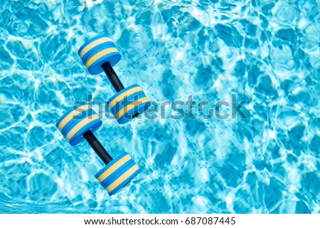 Top view - pair of dumbbells for aqua aerobics float on the surface of water in swimming pool on a warm summer day