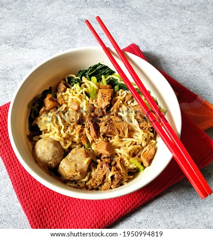 Top view photo of a chicken noodle dish with meatballs and vegetables. Indonesian food Mie Ayam served in a white bowl on a red napkin with red chopsticks.  Zdjęcia stock ©