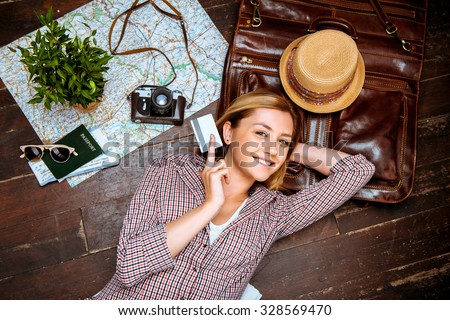 Top view photo of beautiful blonde girl lying on wooden floor. Young woman smiling, holding credit card and looking at camera. Passport, tickets, vintage camera, hat and map are on floor #328569470