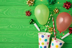 Top view photo of birthday composition blast from paper dotted cups of tinsel sparkles red green golden ribbon stars straws pipes and balloons on isolated green wooden background with copyspace