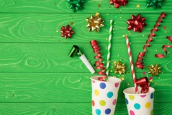 Top view photo of birthday composition blast from paper dotted cups of tinsel sparkles red green golden ribbon stars straws pipes and serpentine on isolated green wooden background with copyspace