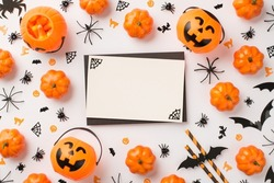 Top view photo of black envelope cobweb on white card pumpkin baskets candy corn straws spiders cats witches and bats silhouettes on isolated white background with blank space