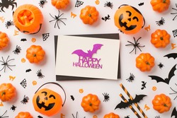 Top view photo of black envelope glitter purple bat inscription happy halloween on white card pumpkin baskets candy corn straws spiders web cats witch and bats silhouettes on isolated white background
