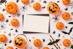 Top view photo of black envelope white card pumpkin baskets candy corn straws spiders cats witches and bats silhouettes on isolated white background with empty space