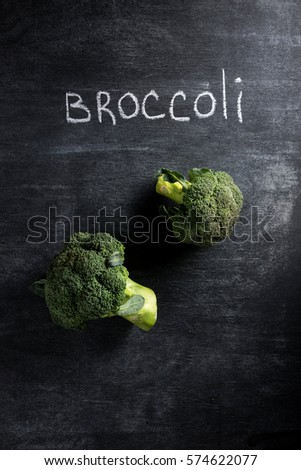 Top view photo of broccoli over dark chalkboard background.