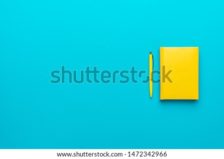 Top view photo of closed yellow notebook and ball-point pen over turquoise blue background with copy space. Minimalist flat lay image of closed diary and yellow pen as back to school background.