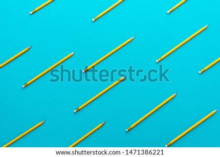 Top view photo of graphite yellow pencils with eraser laid out over turquoise blue background. Minimalist flat lay image of sharpened pencils. Back to school background made of new pencils.
