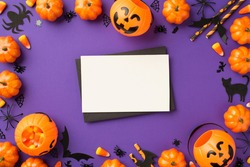 Top view photo of halloween decorations pumpkin baskets candy corn spiders web cat bats silhouettes straws black envelope and white card on isolated violet background with blank space