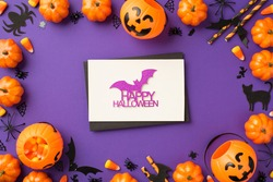 Top view photo of halloween decorations pumpkin baskets candy corn spiders web cat silhouette straws black envelope glitter purple bat inscription happy halloween white card isolated violet background