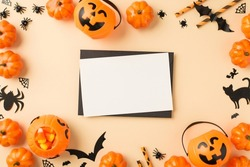 Top view photo of halloween decorations pumpkin baskets candy corn straws spiders cobweb bats cat silhouettes black envelope and white sheet in the middle on isolated beige background with empty space