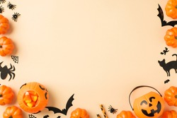 Top view photo of halloween decorations pumpkin baskets candy corn straws spiders web bats and black cat silhouettes on isolated beige background with copyspace
