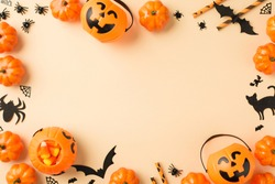 Top view photo of halloween decorations pumpkin baskets candy corn straws spiders web bats and black cat silhouettes on isolated beige background with empty space in the middle
