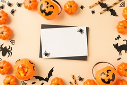 Top view photo of halloween decorations pumpkin baskets candy corn straws spiders web bats cat silhouettes black envelope and white card in the middle on isolated beige background with blank space