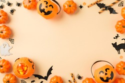 Top view photo of halloween decorations pumpkin baskets candy corn straws spiders web bats ghost and black cat silhouettes on isolated beige background with copyspace in the middle