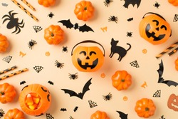 Top view photo of halloween decorations pumpkin baskets candy corn straws spiders web cats and bats silhouettes on isolated beige background