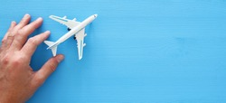 top view photo of man's hand holding toy airplane over blue wooden background