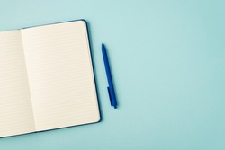 Top view photo of open blue reminder and pen on isolated pastel blue background with copyspace