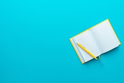 Top view photo of opened notebook and yellow pen over it on turquoise blue background with copy space. Minimalist flat lay image of blank diary and ball-point pen