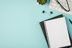 Top view photo of planners pen binders plant and glasses on keyboard on isolated pastel blue background with copyspace