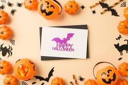 Top view photo of pumpkin baskets candy corn straws spiders web bats cat silhouettes black envelope and white card with purple glitter bat and inscription happy halloween on isolated beige background