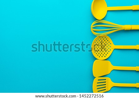 Top view photo of vivid plastic kitchen utensils. Flat lay image of yellow ladle, whisk, skimmer spoon and spatulas over turquoise blue background with copy space.