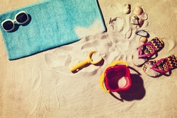 Top view photograph of sandy beach with summer accessories and copy space around objects. Horizontal photo taken from above with visible sand texture. Vintage, retro effect processing.
