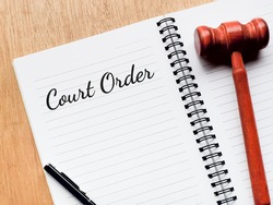 Top view phrase Court Order written on note book with a pen and gavel. Law concept.