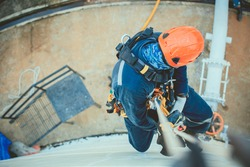 Top view pic of industrial rope access welder working at height wearing harness, helmet safety equipment rope access inspection of thickness storage tank industry.