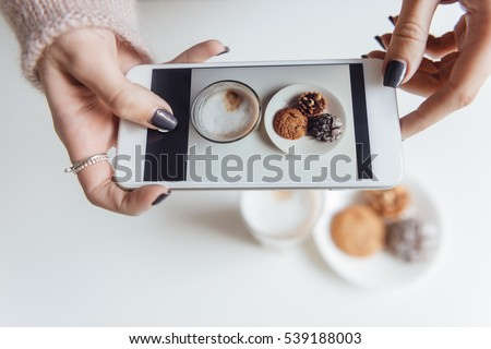 Top view picture of lady sitting in cafe and making photo of food.
