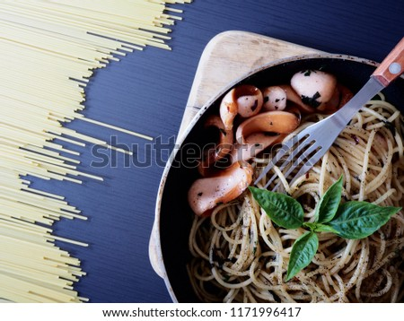 Top view picture of spaghetti spicy sausage on pan above black wooden texture decorate with spaghetti.
