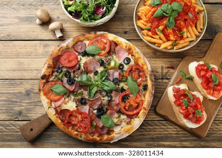 top view pizza pasta with tomato sauce and salad bowl on rustic table