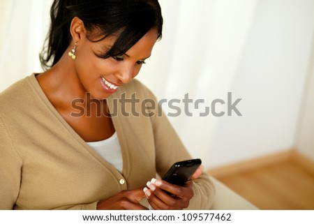 Top view portrait of a charming adult girl reading a message on cellphone