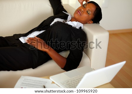 Top view portrait of a young executive woman lying on sofa with eyes closed and headache in front of her laptop