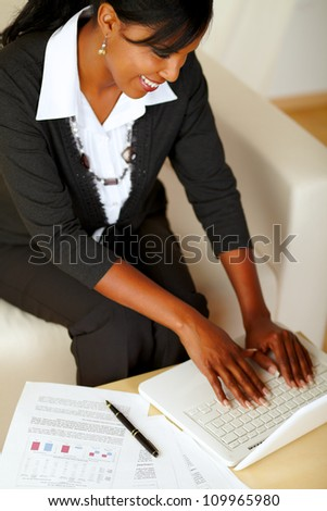 Top view portrait of an attractive businesswoman working on laptop on black suit while sitting on sofa