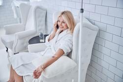 Top view portrait of blonde Caucasian pretty female in white plush bathrobe sitting in style chair while receiving treatment vitamin drip in medicine clinic