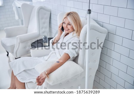 Top view portrait of blonde Caucasian pretty female in white plush bathrobe sitting in style chair while receiving treatment vitamin drip in medicine clinic ストックフォト ©