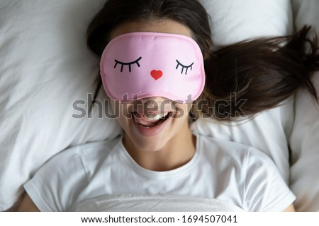 Top view portrait of happy girl lying in comfortable bed wake up in morning have fun making funny faces, smiling young woman in eye sleeping mask awaken in cozy bedroom feel optimistic at home