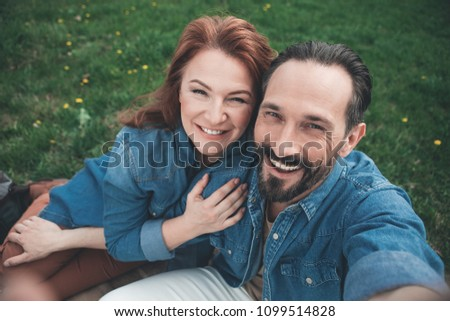 Top view portrait of happy married couple making selfie while relaxing on the meadow. They are embracing and smiling. Man is stretching arm forward
