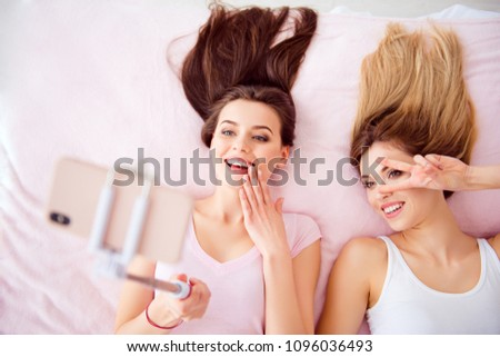 Top view portrait of  joyful, attractive girls with blonde, brunette hair laying on bed on back shooting selfie on front camera using smart phone, selfish stick, gesture peace symbol near eye