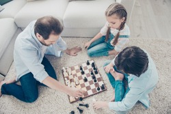 Top view portrait of serious gamers thoughtful concentrated daddy with two kids playing chess sitting on carpet spending time together indoor. Family with one single parent sister brother concept