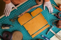 Top view process of cutting scheme of bag with equipment and materials. Craftsman hands measurement and chopping details of leatherwork on table. Male tanner working at leather workshop