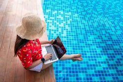 Top view raveler woman in hat sit on modern luxury pool using laptop computer, Businesswoman on vacation at private resort, Attraction leisure tourist travel and work in Phuket Thailand summer holiday