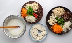 Top view raw material ready to cook homemade rice noodles roll, vegan ingredient as wood ear mushroom, carrot, rice batter, tofu that chopped on white background, Vietnamese popular dish