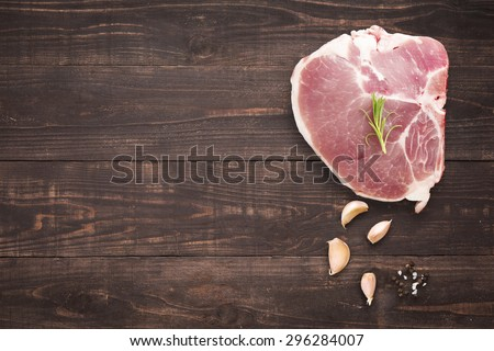 Top view raw pork chop steak and garlic, pepper on wooden background.