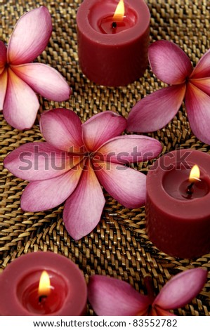 Top view red frangipani flower with burning candle on burlap texture