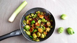 Top view roasted brussel sprouts with crispy bacon and leeks in a pan