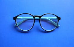 top view round black Eye Glasses on blue pastel Background