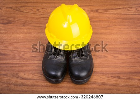 Top view safety shoes and composition of working tools on wooden table